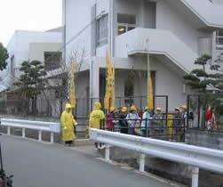 小学校校門前で活動するモデル事業指定団体